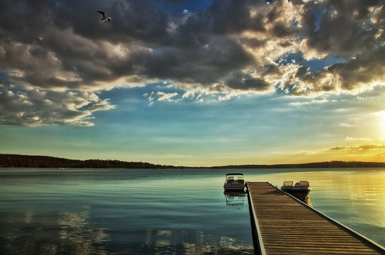 Motor boats moored on a jetty on Lake Macquarie, Australia at sunset