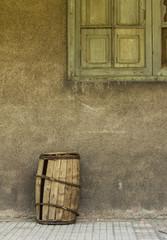 Viejo barril junto a pared deteriorada