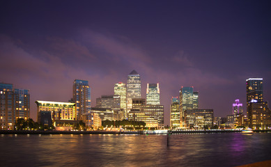 London, Canary Wharf in night with lights reflection in Thames water