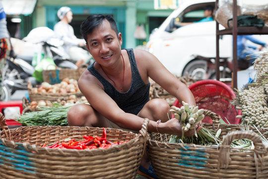 Asian man street market seller bunch green onion