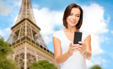 woman with smartphone over eiffel tower