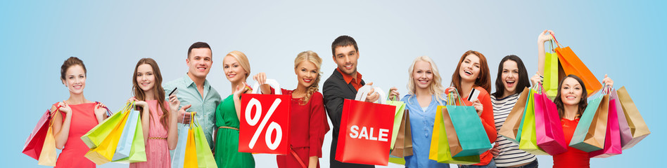 happy people with sale sign on shopping bags