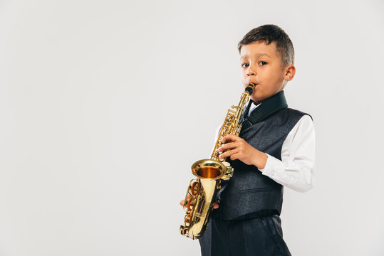 six years old boy plays saxophone at studio