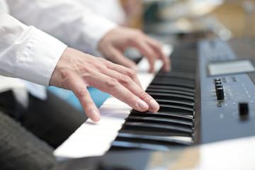 player pianist fingers on keyboard close up
