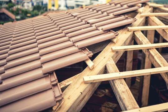 Construction site of new house, roof building with brown tiles and timber. Contractor building roof of new house