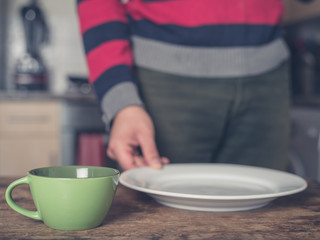 Man setting table in kitchen
