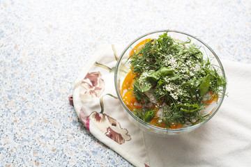 Salad of fresh yellow tomatoes and cucumber with herbs and sesame seeds in a glass bowl on a table
