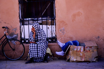 Moroccan life moments / a Moroccan woman waiting sitting next to a bicycle while a man rests in a cardboard box