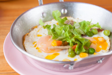 Fried eggs in a pan with vegetables,