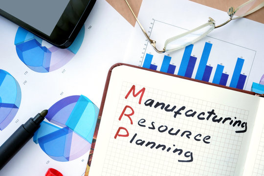 Notepad with words MRP manufacturing resource planning  concept and marker.