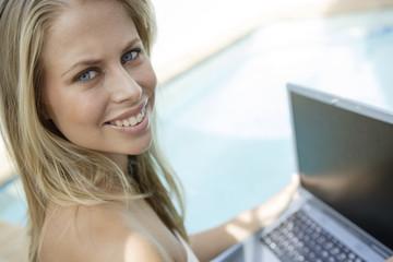 Junge attraktive Frau sitzt mit Laptop am Pool
