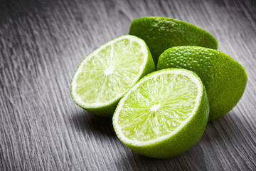 Fresh limes cut in half on wooden surface