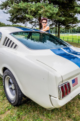 Femme devant une voiture américaine de collection