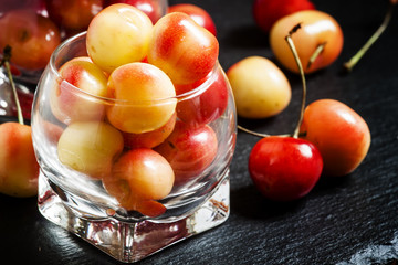 Red and yellow ripe cherries in a glass bowl, selective focus