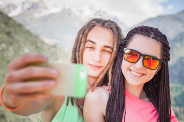 Happy people make selfie on mobile phone at mountain outdoor