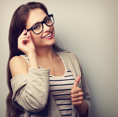 Happy natural smiling young woman in glasses showing thumb up. C