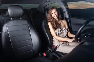 Charming young woman behind the wheel looking at the camera shot through the glass Outdoors