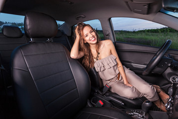 Beautiful young smiling woman in the car and going to travel Outdoors