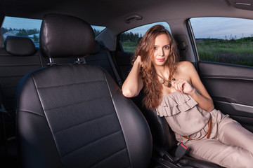Beautiful girl in the driver's seat looking at the camera and has a journey Outdoors