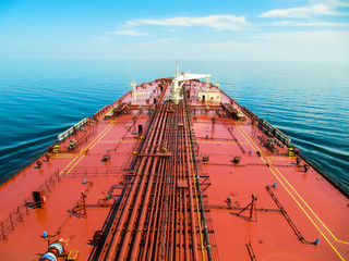 Oil tanker is proceeding in blue ocean under cloudy sky - stock photo