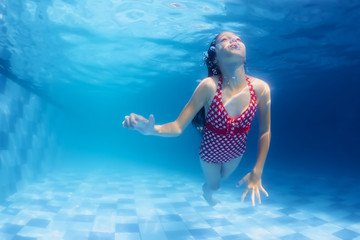 Child swimming underwater lesson - girl diving with fun in blue pool Healthy active family lifestyle, physical development and children water sport activity with parents on summer vacation with kids