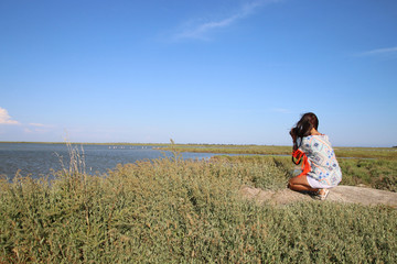 young woman taking a picture of a camargue pond