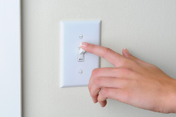 Woman turning off light switch