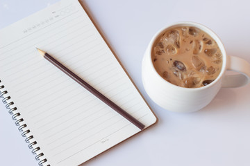Open a blank white notebook, pencil  and iced coffee isolate on white background.