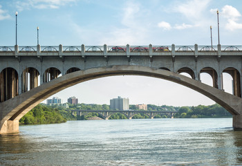 horizontal image of an arched concrete bridge framing skyscrapers and trees in the background with a river flowing underneath and a blue sky in the summer time