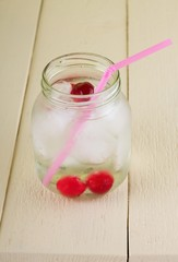 Cold cherry drink in jar with pink straw