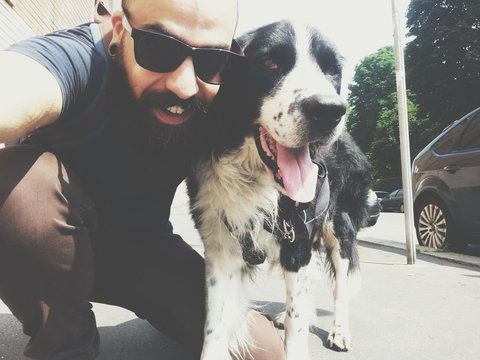 Bearded man and his dog friend taking selfie