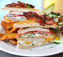 Clubsandwich mit Kartoffelspalten und Salat