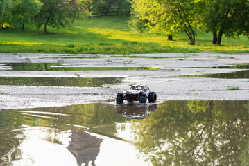 radio controlled monster truck performing a trick at high speed jumps over a large puddle. soft focus and beautiful bokeh