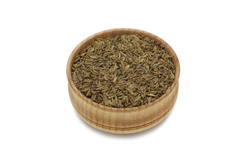 cumin seeds in a wooden bowl on a white background