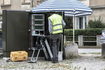 elettricista ripara quadro elettrico sotto l'ombrellone