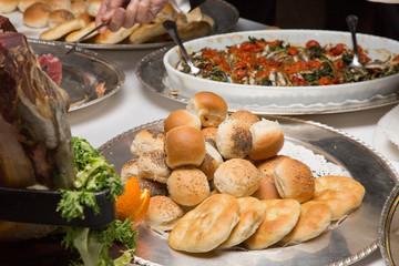 Buffet con vassoi argento, panini e pizzette in primo piano