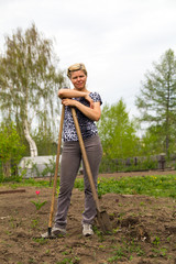 Positive smiling blonde with a shovel and rake in the garden