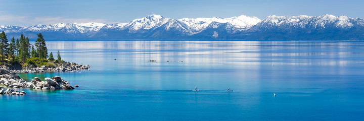 Paddle boarding calm Lake Tahoe with view on Sierra Nevada snowy mountains.