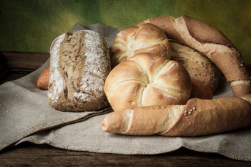 various rolls of wheat on a background of a wooden table