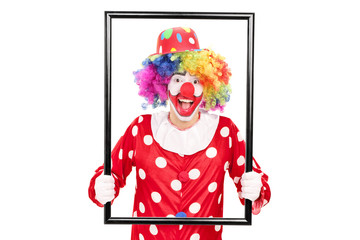 Male clown holding a big picture frame and posing behind it