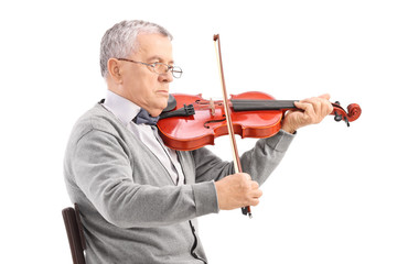 Senior musician playing an acoustic violin seated on a wooden ch