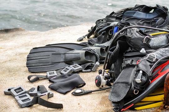 Pile of Scuba Diving Equipment Drying on Dock