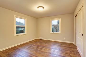 Simple hardwood floor bedroom with windows.