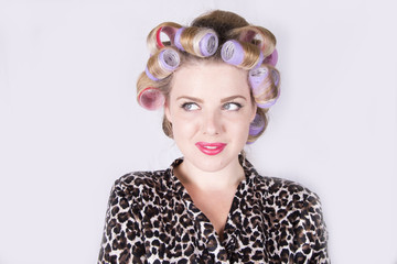 Beautiful blonde woman with curlers wearing a leopard print bathrobe (studio portrait)