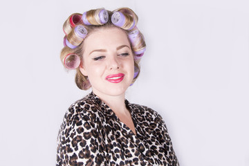 Beautiful blonde woman with curlers wearing a leopard print bathrobe (studio portrait)