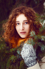 Attractive young woman with curly hair near pine tree