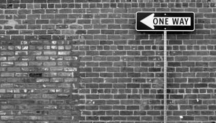 One Way street sign in black and white with brick building