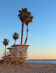 Life guard tower with palm trees as the sun sets in California