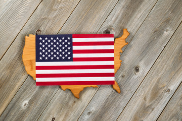 Flag over top of United States of America Shape on rustic wooden