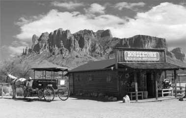Old black and white Wild West Cowboy town with horse drawn carriage and mountains in background